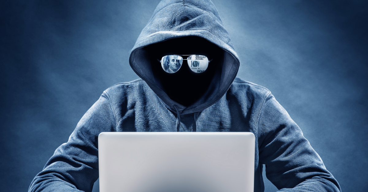 Person with Mask and Sunglasses on Computer Committing Fraud