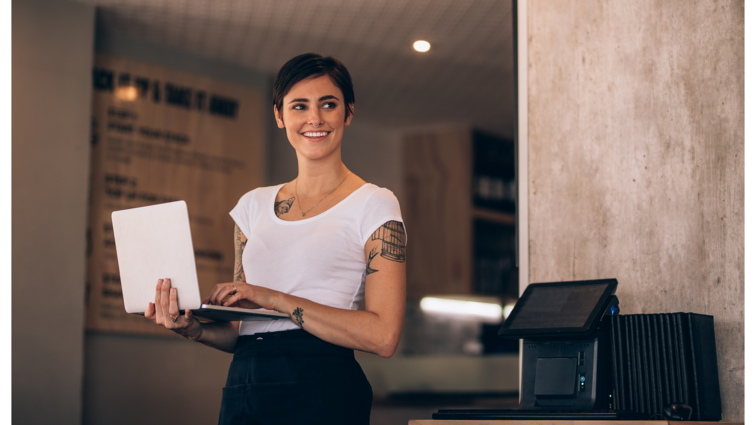 Woman standing holding laptop smiling