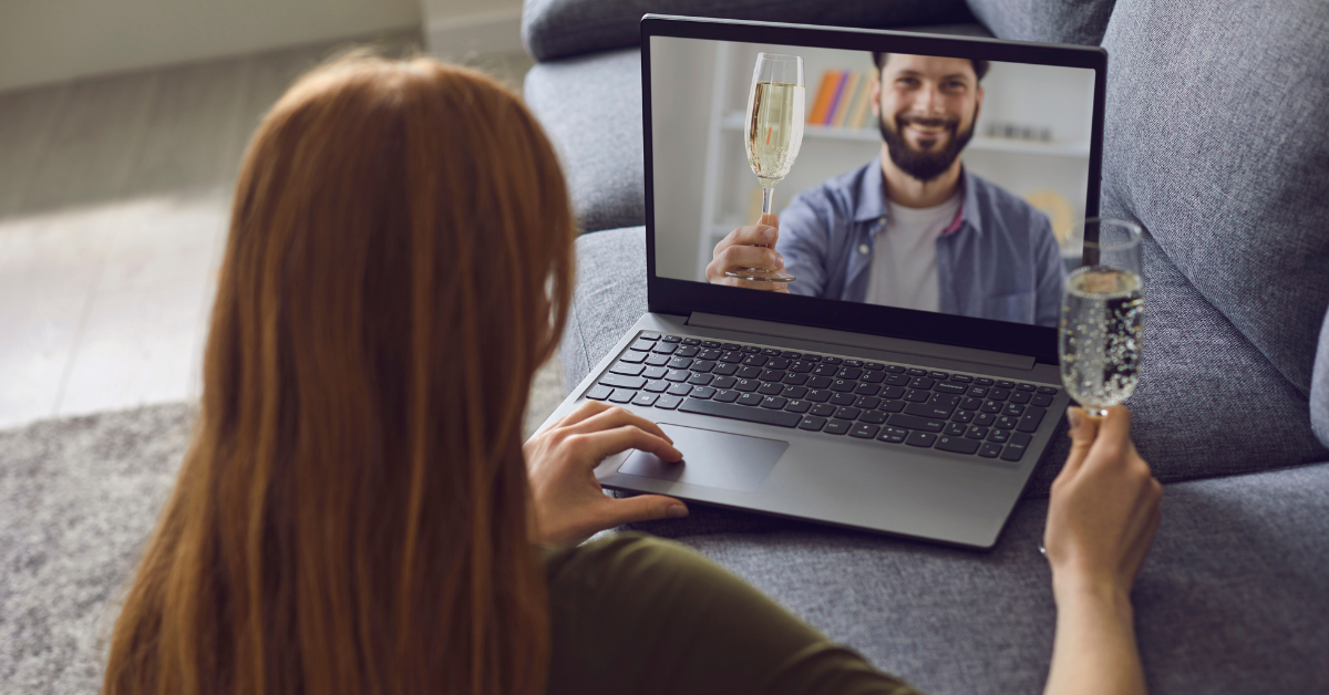 Woman holding champagne on video call with a male also holding champagne